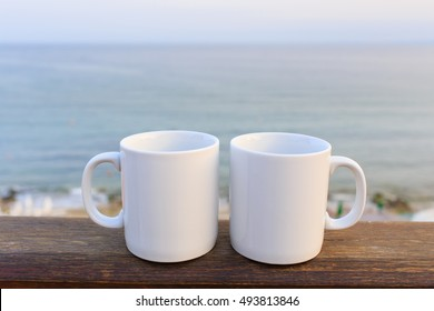 Two white mugs on balcony in front of sea