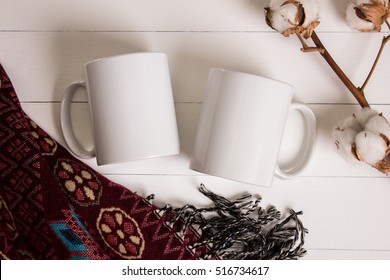 Two white mugs, pair of cups, Mockup. Cozy atmosphere, wooden background, cotton and wool decorations for winter gifts.