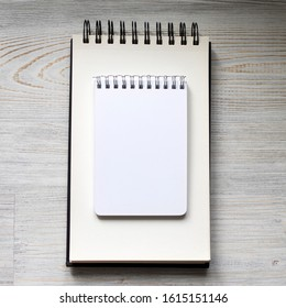 two white notebooks for writing different shapes lie on the table