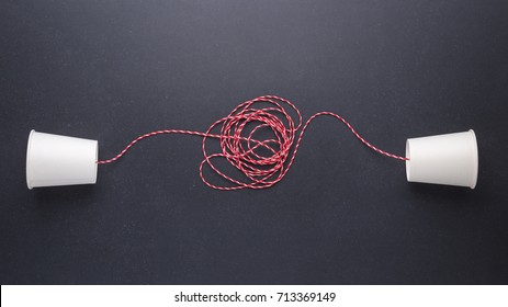 Two white paper cup connect with red rope used for classic phone on black stone table board background. For old communication system concept