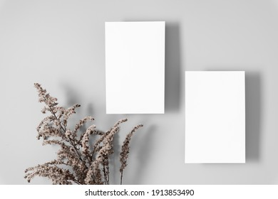 Two white paper empty blank, dried flowers on gray table. Invitation card mockup. Flat lay, top view, copy space, mockup