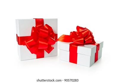Two white pasteboard square gift boxes with red satin bow and ribbon isolated on white background with clipping path.