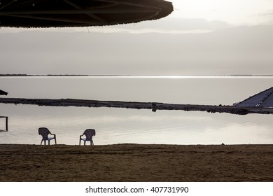 Two white plastic chairs and sunshades at lonely beach in the early morning