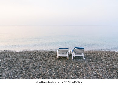 Two white plastic deckchairs on the sea beach at sunset. Summer vacation concept.
