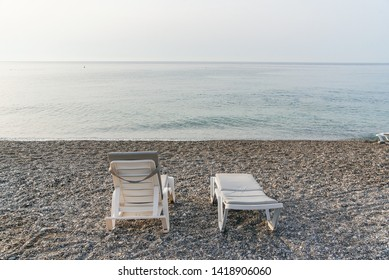 Two white plastic deckchairs on the sea beach at sunrise. Summer vacation concept. Back view.