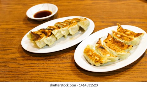 Two white plates with Japanese dumplings (Gyoza) on a wooden table with a small plate for gyoza sauce in a restaurant