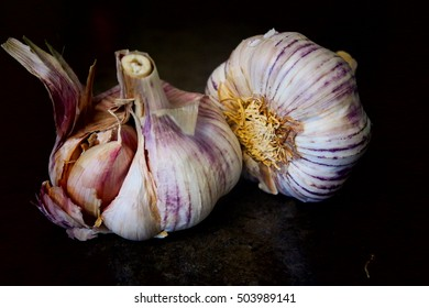 Two white and purple garlic in the black background