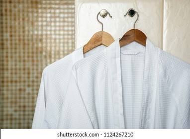 cd018b1dfa Two white rag bathrobes towels on wooden hangers in the interior of a  stylish bathroom.