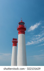 Two white and red lighthouses isolated on a blue and cloudy sky