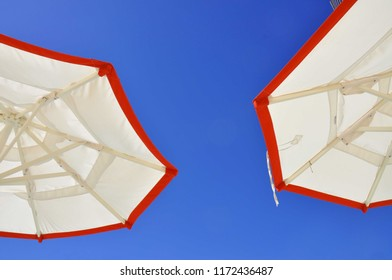 Two white and red trimmed beach umbrellas against a bright blue sky.