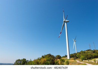 Two white and red wind turbines on a green hill with clear blue sky and power lines. Verona, Italy