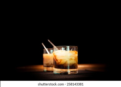 Two white russian cocktails on the bar stand on rubber mat. Shallow DOF and marsala tonned