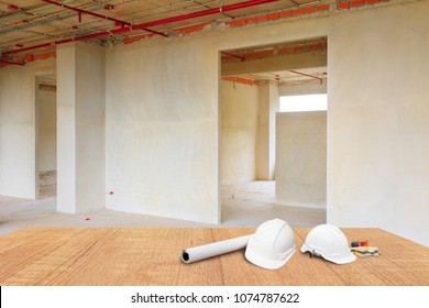 two white safety helmet and leather glove Measuring Tape, roll paper plan blueprint for engineering working interior construction site building on wood floor table with copy space. blur background