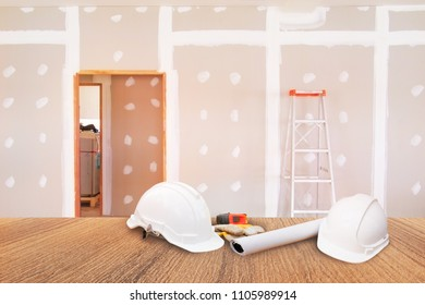 two white safety helmet plastic white roll paper blueprint on Wooden floor in room work gypsum board wall interior decoration of home construction site