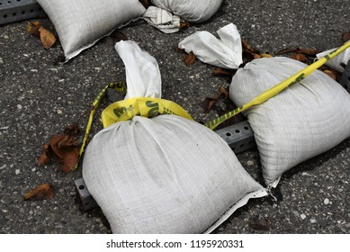 Two white sandbags in use on a road to hold down a street sign.  Caution tape, reconstruction area, leaves and black top.