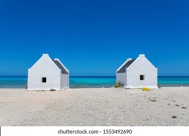 Two white slave houses on beach with blue sea on island Bonaire
