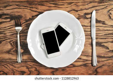 Two white smartphones with big black screens on the plate with silver knife and fork on the dark wooden background