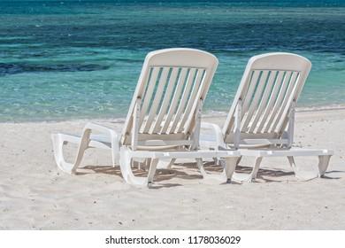 Two white sunbeds on a sandy beach facing the Caribbean Sea.