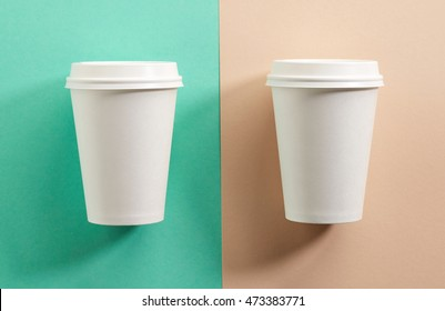 two white take away coffee cups on colorful paper background