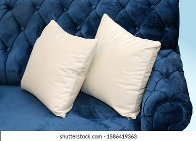 Two white textile pillows in corner of retro blue couch