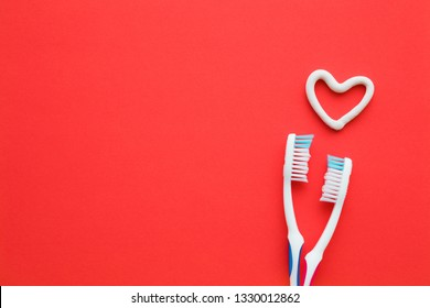 Two white toothbrushes on bright red background. Heart shape created from toothpaste. Man and woman teeth hygiene. Living together. Love concept. Empty place for lovely, cute text, quote or sayings.