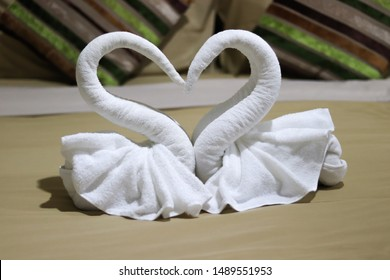 Two white towels Were folded like a swan Being laid face-to-face, looking like a heart shaped on a bed in the bedroom used as an illustration