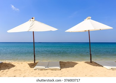 Two white umbrellas and blue sky on Surin beach in Phuket Thailand