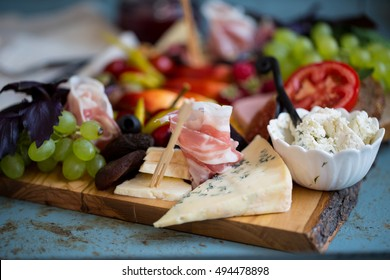 Two white wine glasses with cheese platter with fruits and meats