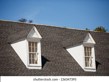 Two white wood dormers on a grey shingle roof under blue sky