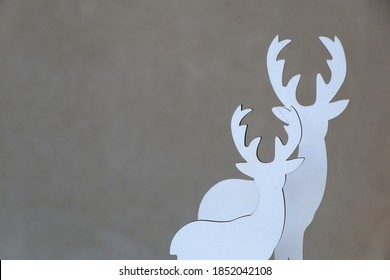 Two white wooden deer figurines in front of a concrete wall. Minimal Christmas decorations.