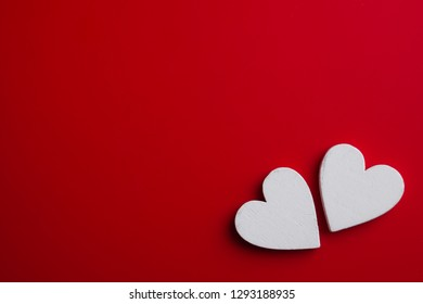 Two white wooden hearts on red background. Top view Valentines pattern.