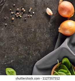 Two Whole Bulbs, a Gray Napkin, Peppercorns, Spinach and Garlic on a Black Stone Background top view. Dark Slate Frame with Flat Lay Spices for Recipe Template