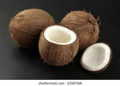 Two whole coconuts and one opened photographed on black background