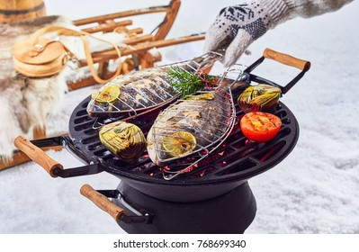 Two whole fish grilling over a winter barbecue outdoors in fresh white snow with a gloved hand turning them over the coals