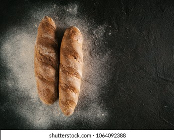 Two whole homemade buckwheat loaf bread with buckwheat flour on black textured background. Top view or flat-lay. Copy space. Low key