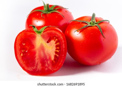 Two whole and one half fresh  greenhouse grown tomatoes on a white surface