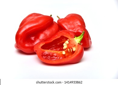 Two whole and one half habanero or Satan's peppers isolated on white