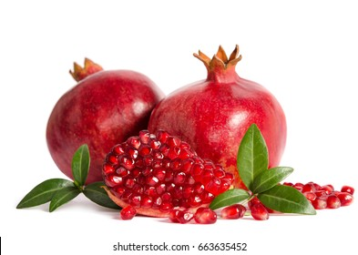two whole and part of a pomegranate with pomegranate seeds and leaves isolated on white background