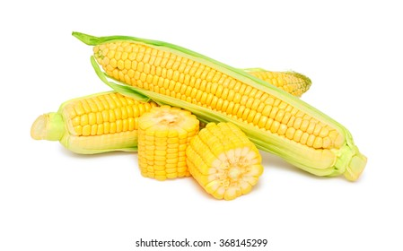 Two whole and pieces of ripe corn on the cob with green leaves isolated