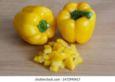 Two whole and pieces of yellow peppers on a table