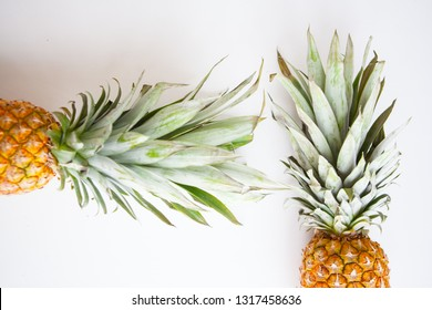Two whole pineapples creatively positioned in a flat lay layout on a white background
