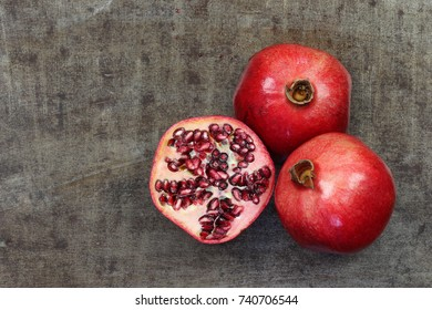 two whole pomegranate (Punica granatum) and a cut one on a grungy metal background