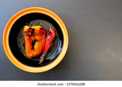 two whole roasted peppers in an orange-rimmed black bowl, top view, black background