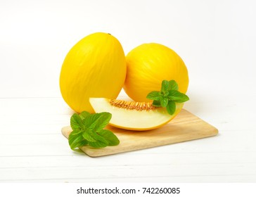 two whole yellow melons and slice of melon next to them on cutting board