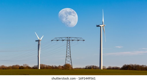 Two wind turbines for wind energy and an electricity pylon with cables in the middle on a field on the Baltic island of Rügen. It is just before sunset and the moon is in the sky.