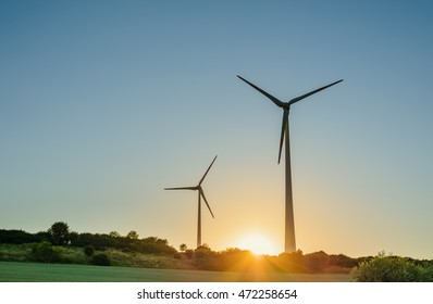 Two wind turbines silhouetted against a blue sky with fiery orb of the sun on the horizon at sunrise or sunset in a renewable energy concept