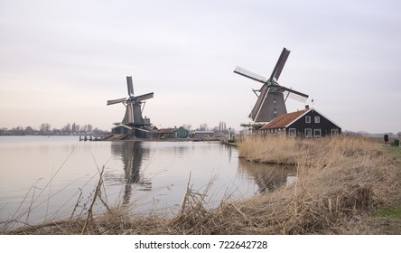 Two windmills alongside Zaans river in winter
