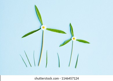 two windmills made of fresh green leaves on blue background, top view, flat lay