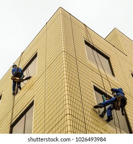 Two window washers at work. Windows washers abseiling down the sides of a building wall on small wooden seats to clean windows during winter in Tokyo , Japan.