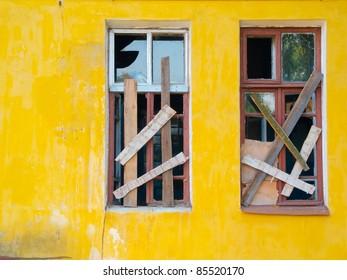 Two windows boarded up with boards in the yellow wall